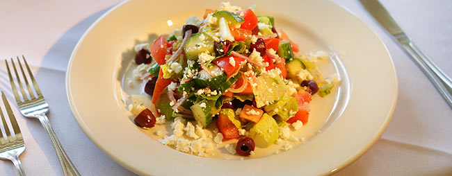 Greek Salad. Mixed greens tossed with kalamata olives, cucumbers, red onion, feta cheese, and a white wine vinaigrette